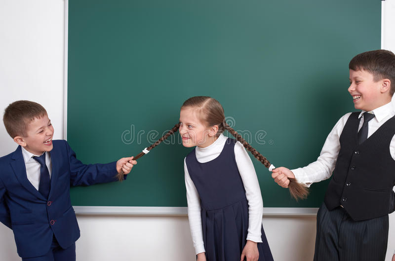 Child play and having fun, boys pull the girl braids, near blank school chalkboard background, dressed in classic black suit, grou royalty free stock photography
