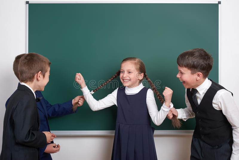 Child play and having fun, boys pull the girl braids, near blank school chalkboard background, dressed in classic black suit, grou stock photo