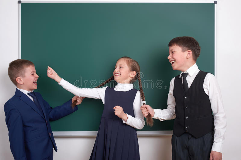 Child play and having fun, boys pull the girl braids, near blank school chalkboard background, dressed in classic black suit, grou stock image