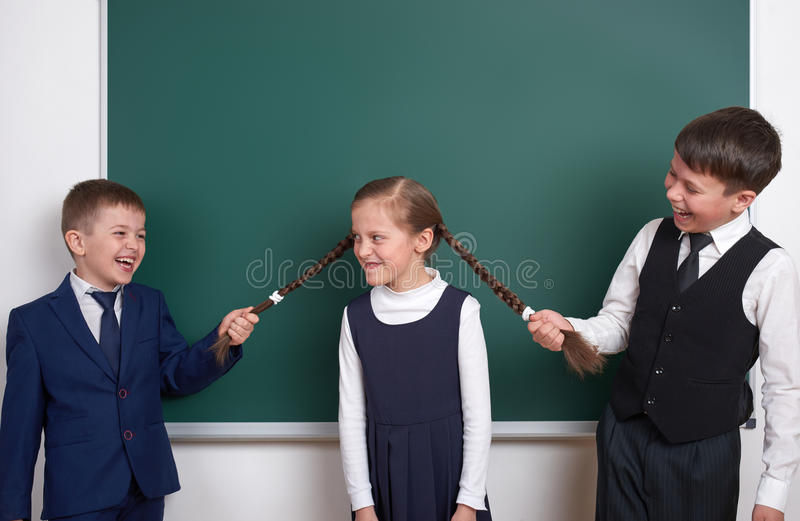 Child play and having fun, boys pull the girl braids, near blank school chalkboard background, dressed in classic black suit, grou royalty free stock images