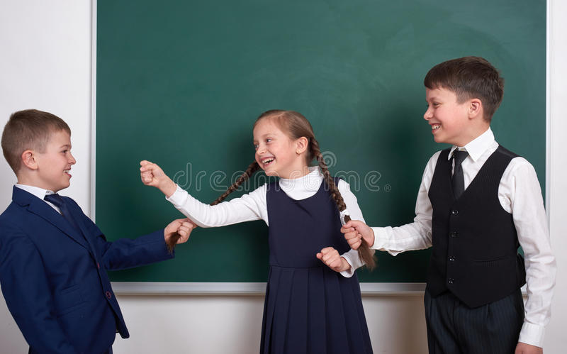Child play and having fun, boys pull the girl braids, near blank school chalkboard background, dressed in classic black suit, grou royalty free stock photo