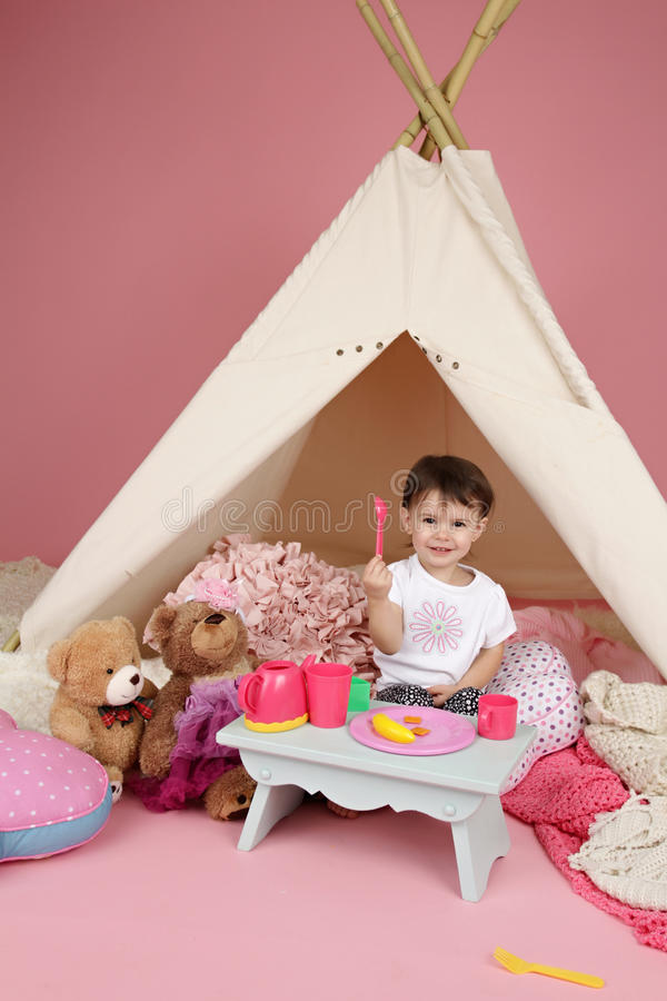 Child Play: Pretend Food, Toys and Teepee Tent. Toddler child, kid, engaged in pretend play with food, stuffed toys, and teepee tent royalty free stock photos