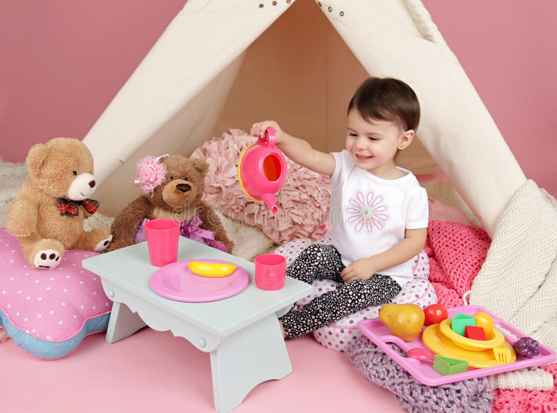 Child Play: Pretend Food, Toys and Teepee Tent. Toddler child, kid, engaged in pretend play with food, stuffed toys, and teepee tent stock photo