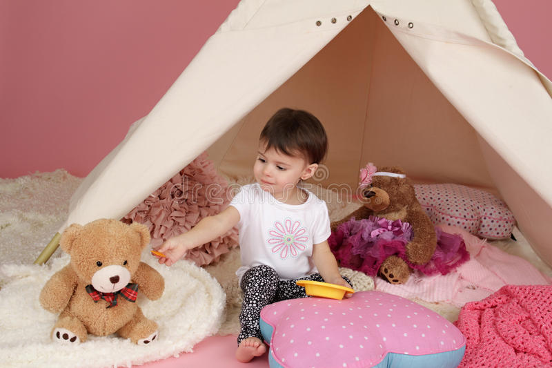 Child Play: Pretend Food, Toys and Teepee Tent. Toddler child, kid, engaged in pretend play with food, stuffed toys, and teepee tent stock photography