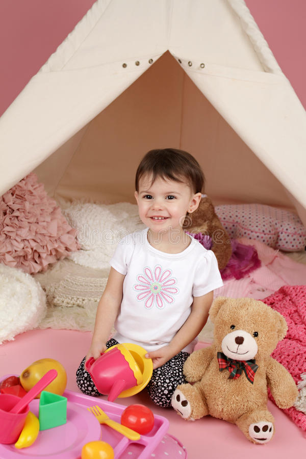 Child Play: Pretend Food, Toys and Teepee Tent. Toddler child, kid, engaged in pretend play with food, stuffed toys, and teepee tent stock images