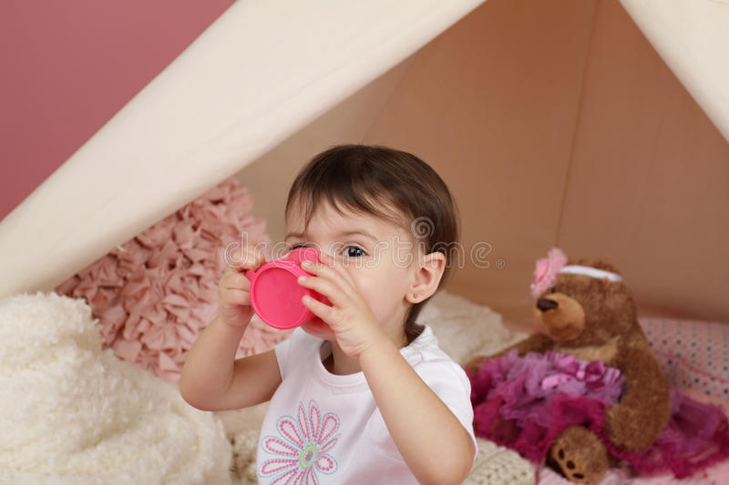 Child Play: Pretend Food, Toys and Teepee Tent. Toddler child, kid, engaged in pretend play with food, stuffed toys, and teepee tent royalty free stock photo
