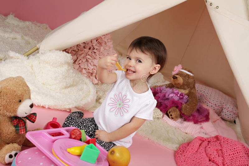 Child Play: Pretend Food, Toys and Teepee Tent. Toddler child, kid, engaged in pretend play with food, stuffed toys, and teepee tent royalty free stock images