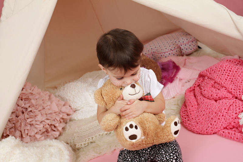 Child Play: Pretend Games Toys and Teepee Tent. Toddler child, kid, engaged in pretend play with stuffed toys, and teepee tent royalty free stock photography