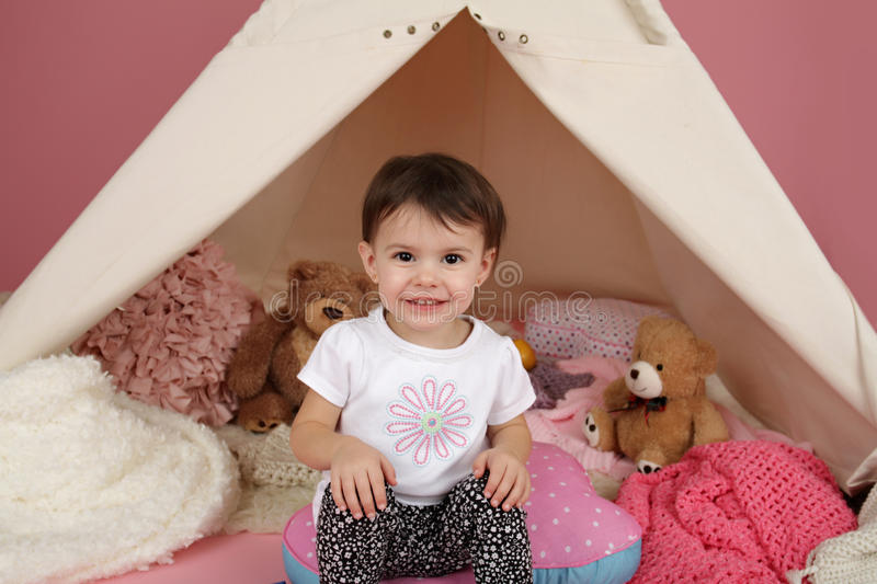 Child Play: Pretend Games Toys and Teepee Tent. Toddler child, kid, engaged in pretend play with stuffed toys, and teepee tent royalty free stock images
