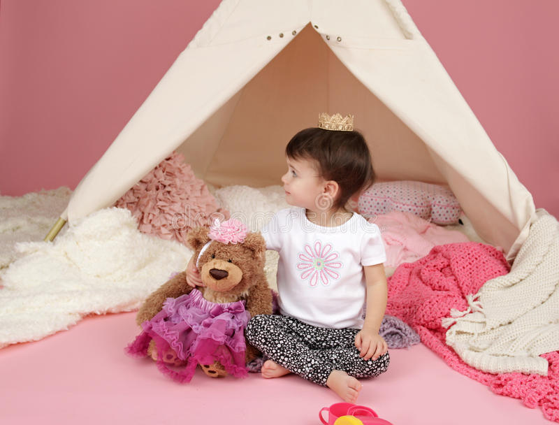 Child Play: Pretend Games Toys and Teepee Tent. Toddler child, kid, engaged in pretend play with stuffed toys, and teepee tent royalty free stock photos