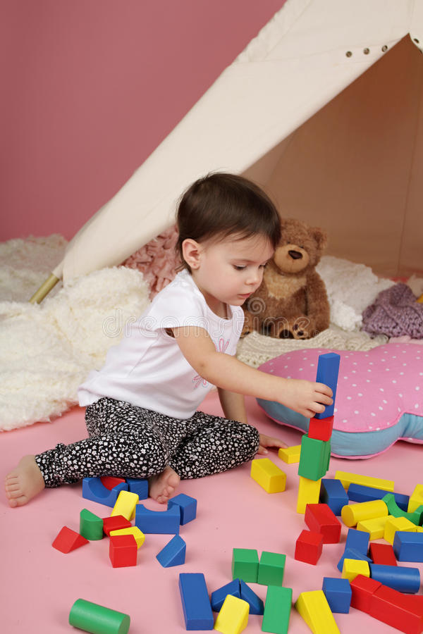 Child Play: Pretend Games Toys and Teepee Tent. Toddler child, kid, engaged in pretend play with stuffed toys, and teepee tent stock image