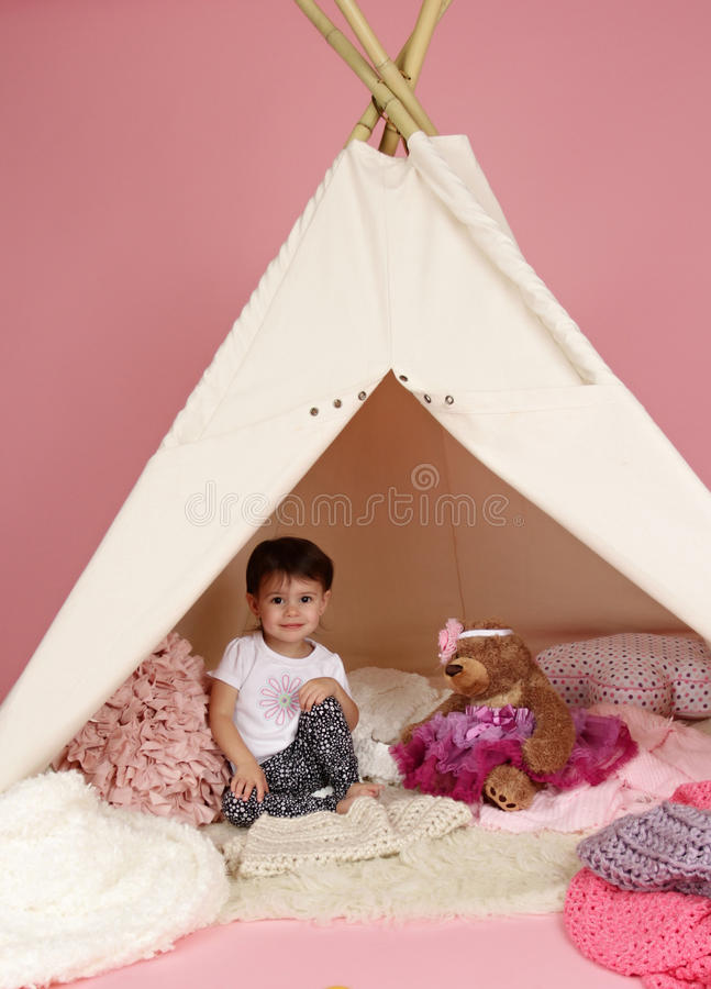 Child Play: Pretend Games Toys and Teepee Tent. Toddler child, kid, engaged in pretend play with stuffed toys, and teepee tent stock photography