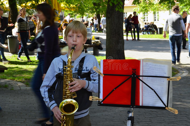 Child play saxophone people walk. Street music day. VILNIUS, LITHUANIA - MAY 2012 - Unidentified child play saxophone. People walk around. Street Musician Day royalty free stock photography