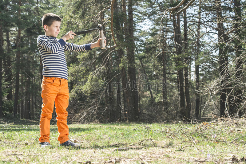 Child play with sling toy. In the forest stock photos