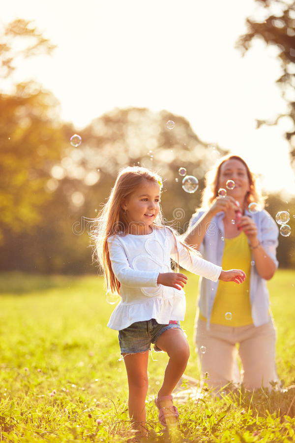 Child play with soap bubbles. Young child play with soap bubbles in park royalty free stock image