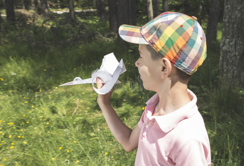 Child play with a stork made of paper. Forest royalty free stock images