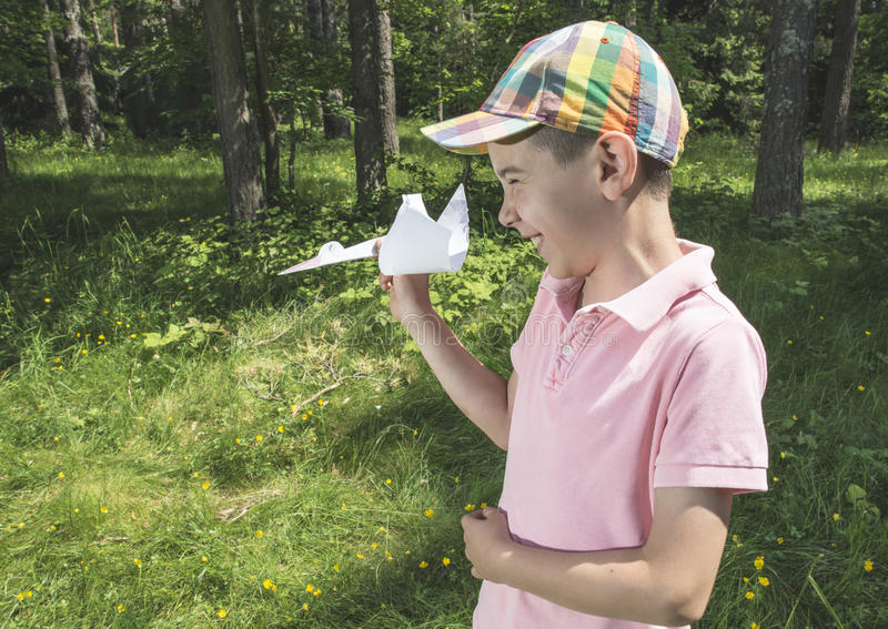 Child play with a stork made of paper. Forest stock image