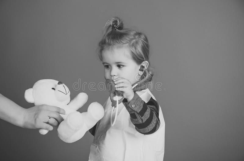 Child play veterinarian with teddy bear in mothers hand royalty free stock photos