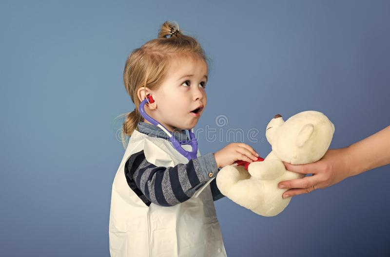 Child play veterinarian with teddy bear in mothers hand. Boy doctor examine toy pet with stethoscope on blue background. Veterinary clinic game. Future royalty free stock photo