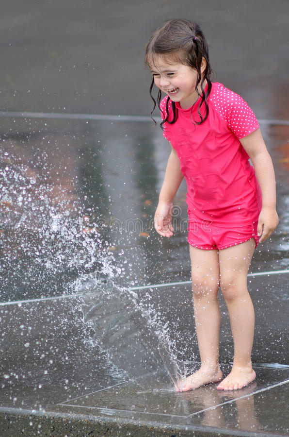 Child play water with water fountain royalty free stock image