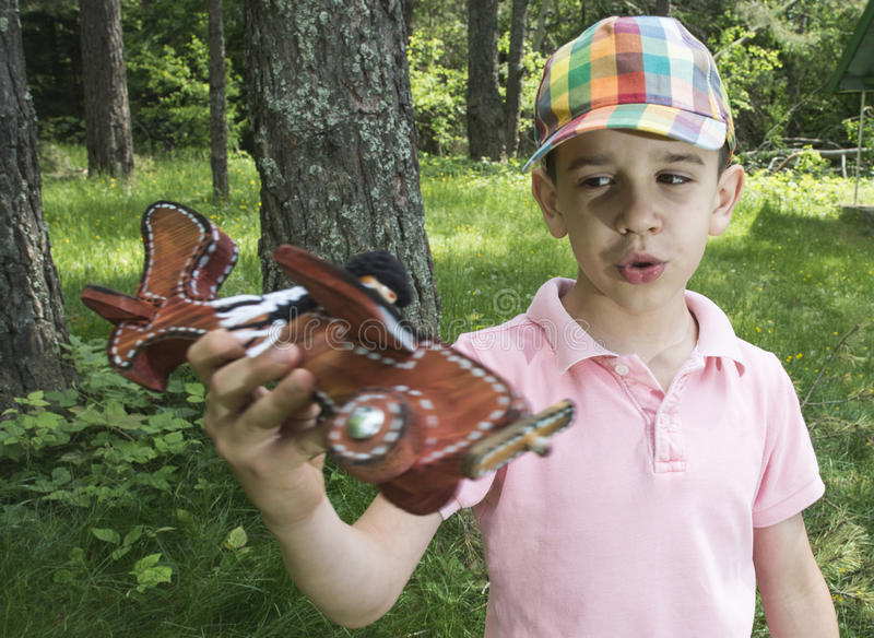 Child play with a wooden plane in the mountain. Forest stock images