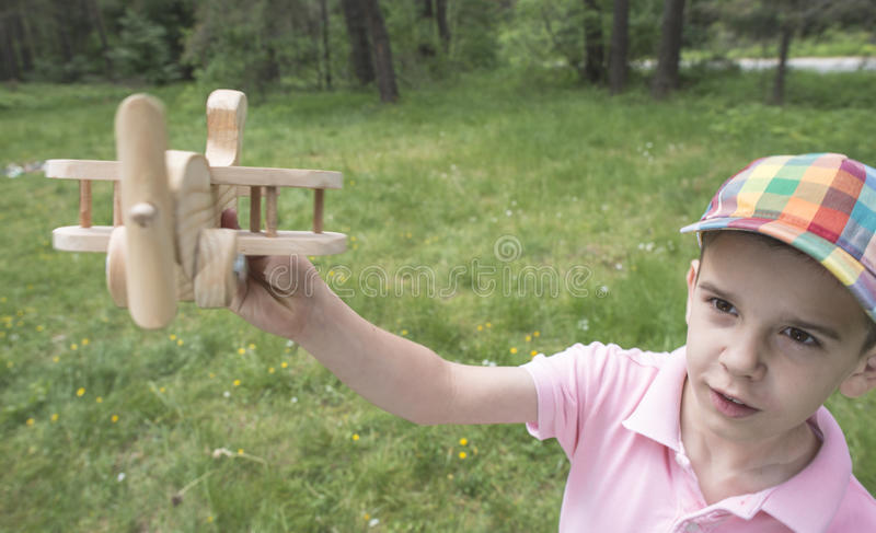 Child play with a wooden plane in the mountain. Forest stock photography