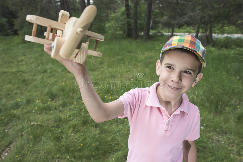 Child play with a wooden plane in the mountain. Forest royalty free stock photos