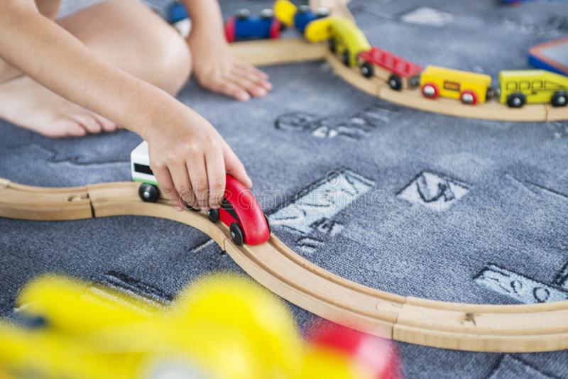 Child play with wooden train, build toy railroad at home or kindergarten. Toddler kid play with wooden train royalty free stock photo