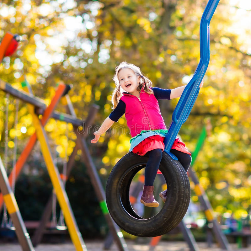 Child on playground in autumn. Kids in fall. Kids on playground Children play in autumn park. Child on slide and swing on sunny fall day. Preschool or royalty free stock photography