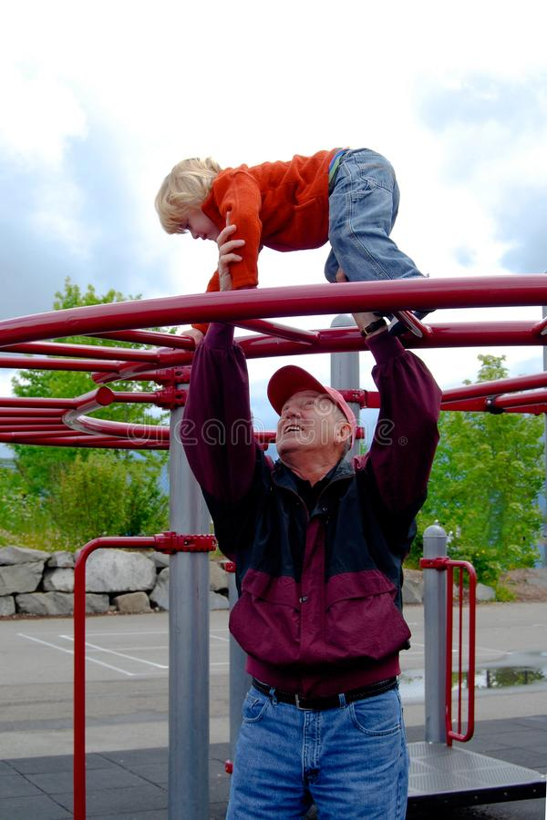 Close up of Child Playing on Playground equipment. Child on playground equipment . Grandfather gives helping hand to keep the fun activity safe royalty free stock image