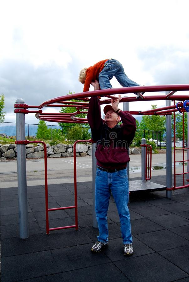 Child Playing on Playground equipment. Child on playground equipment . Grandfather gives helping hand to keep the fun activity safe stock images