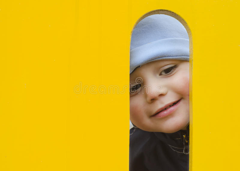 Child at playground. Face of small child, boy or girl, looking through a hole in a play equipment in an outdoors playground stock photos