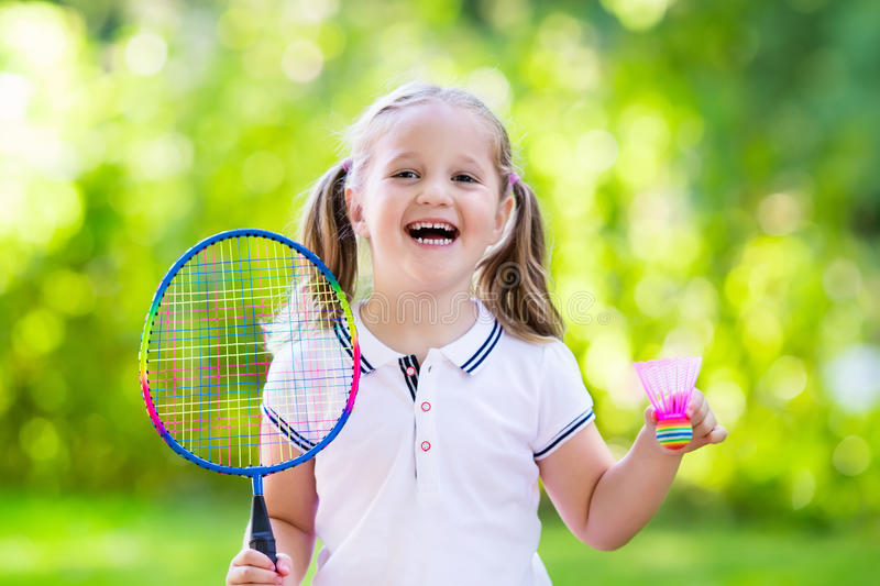 Child playing badminton or tennis outdoor in summer royalty free stock photos