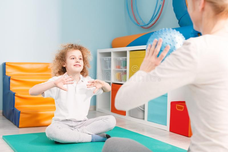 Child playing ball with physiotherapist stock photo