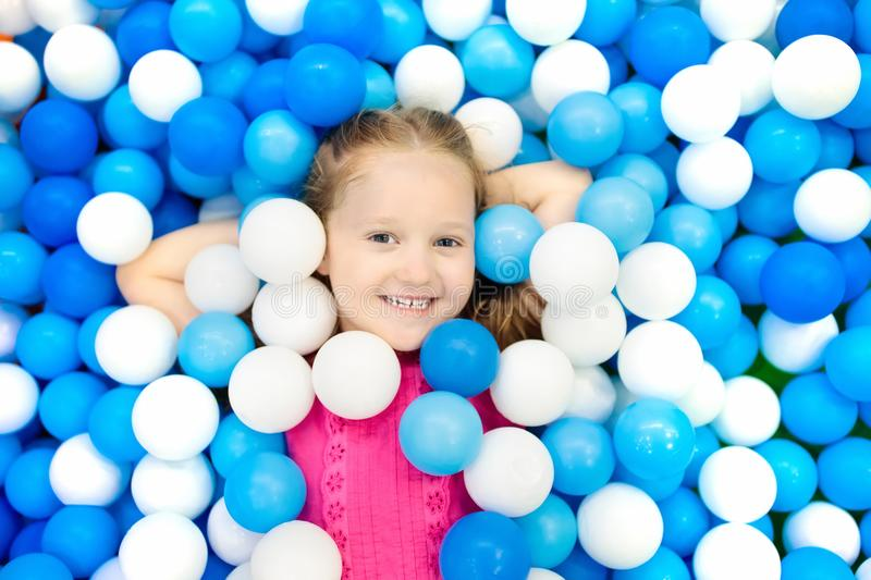 Kids play in ball pit. Child playing in balls pool. Child playing in ball pit. Colorful toys for kids. Kindergarten or preschool play room. Toddler kid at day royalty free stock photo