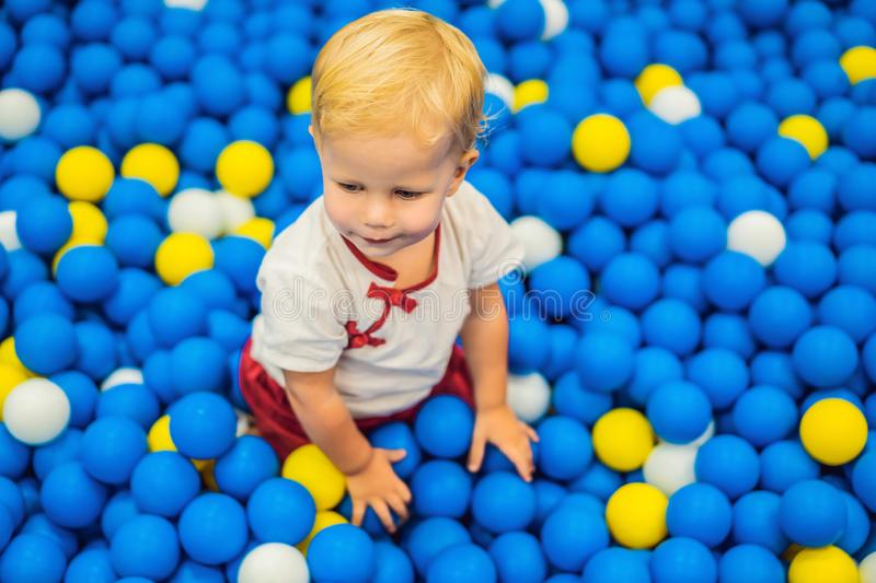 Child playing in ball pit. Colorful toys for kids. Kindergarten or preschool play room. Toddler kid at day care indoor royalty free stock photography