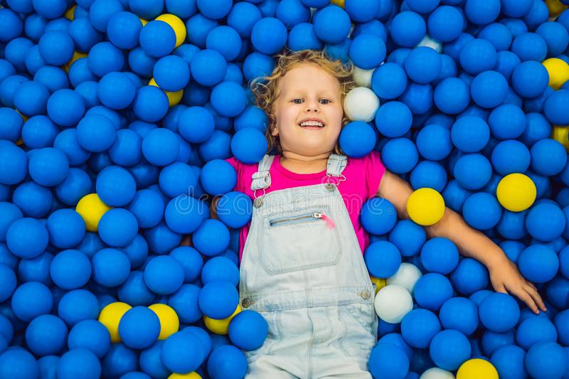 Child playing in ball pit. Colorful toys for kids. Kindergarten or preschool play room. Toddler kid at day care indoor royalty free stock images