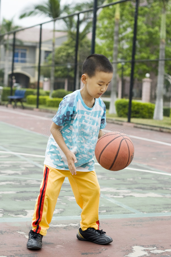A child playing basketball. A Chinese child playing basketball in stadium stock image