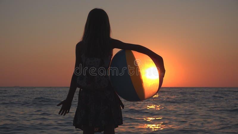 Child Playing Beach Ball in Sunset, Kid Watching Sea Waves, Girl View at Sundown royalty free stock photos