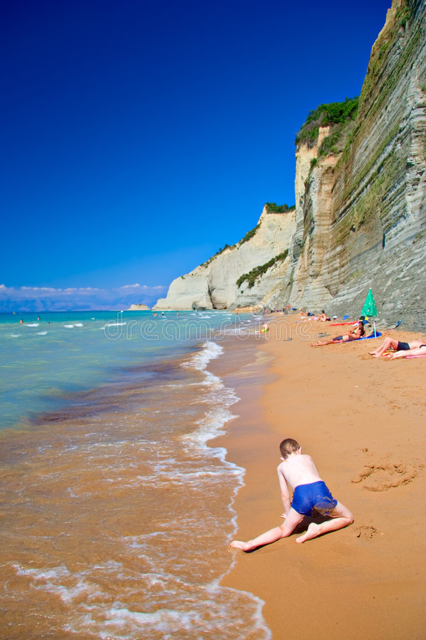 Child playing on the beach at Corfu island royalty free stock photo