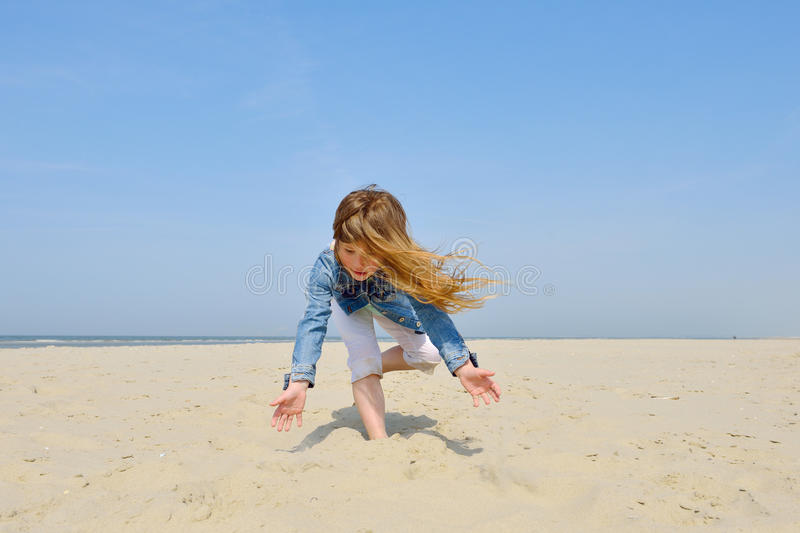 Child playing on the beach. Happy female child playing with sand on spring beach stock photos