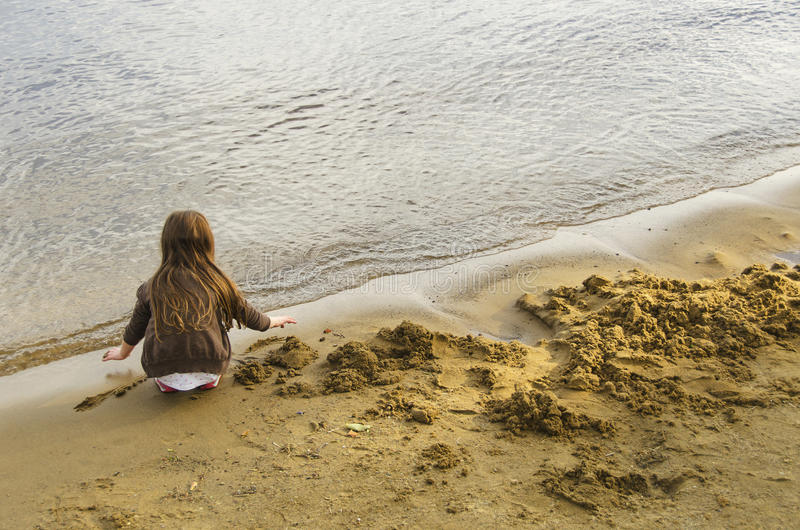 Child playing on beach stock photography