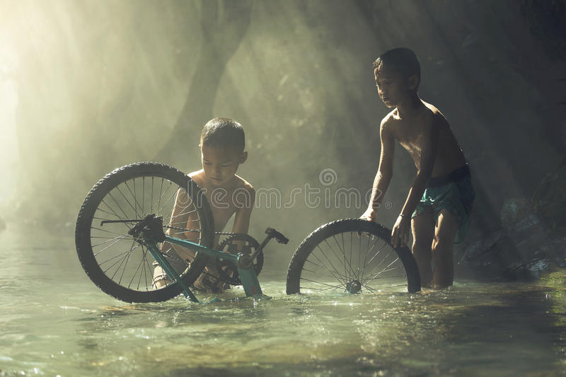 Child playing with bicycle in the creek royalty free stock photo