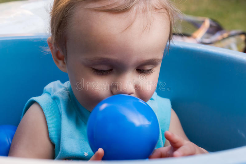 Child playing with blue ball stock photo