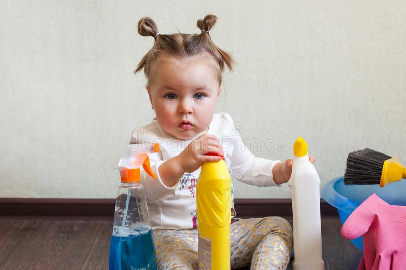 Child playing with bottles with household chemicals sitting on the floor of the house. stock photo