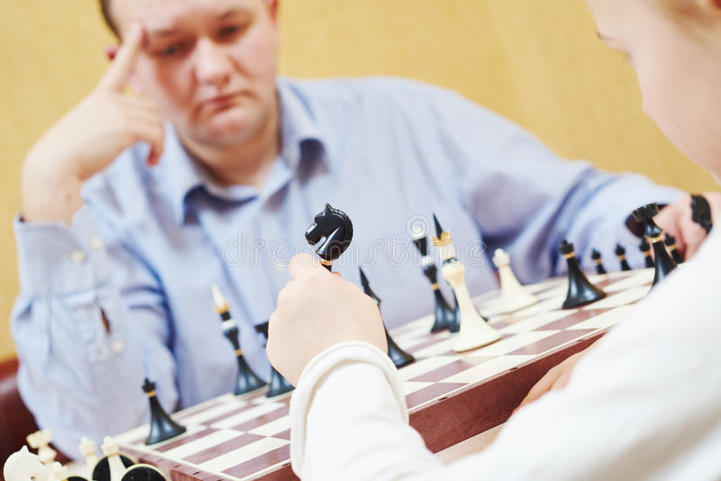 Child playing chess with father stock photography
