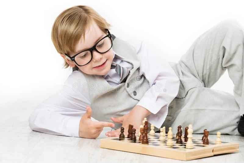 Child Playing Chess, Smart Kid Boy in Business Suit Glasses Play royalty free stock photography
