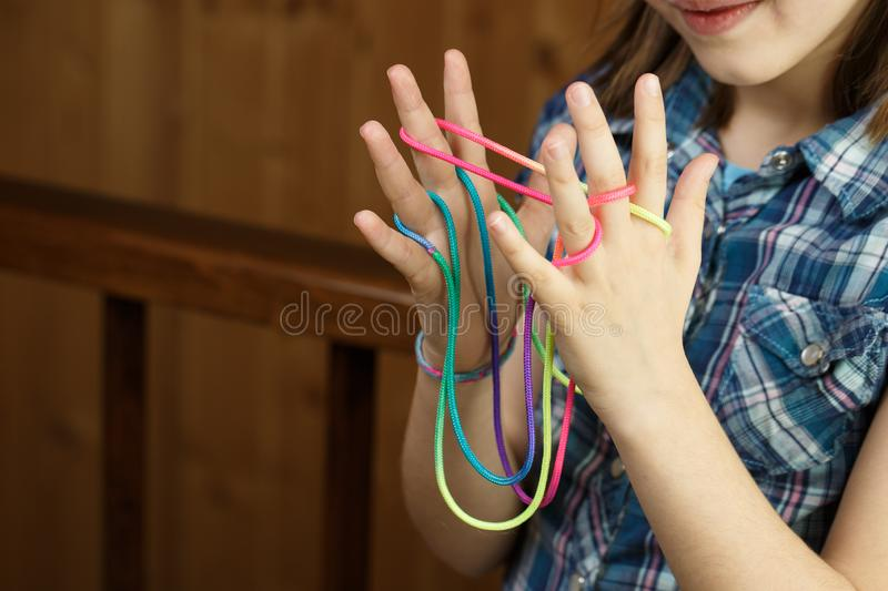 Child playing classic string game, creating shapes stock photos
