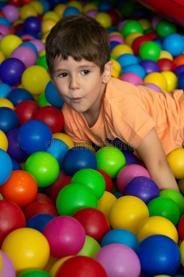 Child playing with colorful balls in playground ball pool. Activity toys for little kid. Kids happiness emotion having fun in ball royalty free stock photos