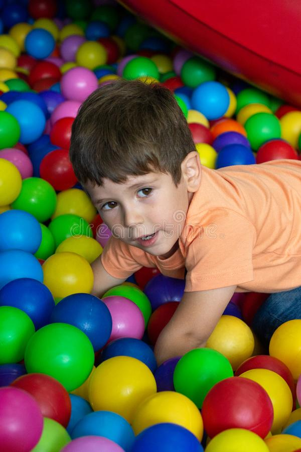 Child playing with colorful balls in playground ball pool. Activity toys for little kid. Kids happiness emotion having fun in ball royalty free stock photo